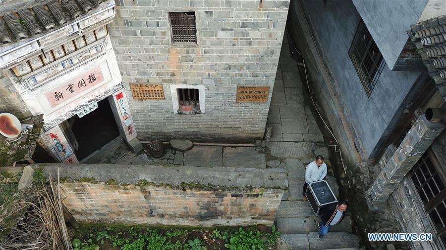 Aerial photo shows Huang Yiyin (front) and his assistant Wang Yangqing carrying the screening facilities in Santangmen Village of Benchu Town, Tianzhu County of Miao and Dong Autonomous Prefecture of Qiandongnan, southwest China\'s Guizhou Province, March 19, 2019. Local authority in Tianzhu County established special fund to show movies in rural areas. In 2018, a total of 14 voluntary projectionists in Tianzhu showed 3,979 movies in villages within the county. (Xinhua/Ou Dongqu)