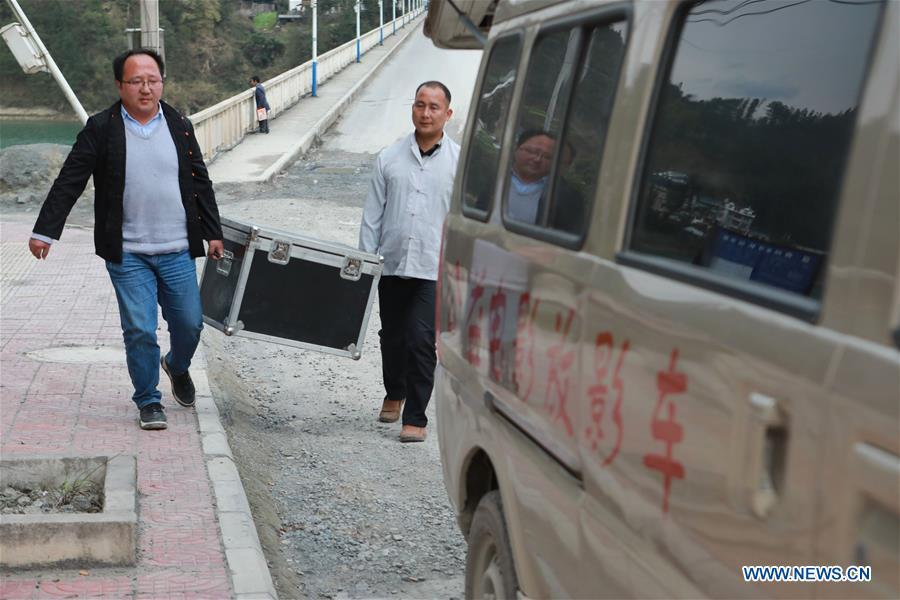 Huang Yiyin (L) and his assistant Wang Yangqing carry the screening facilities in Santangmen Village of Benchu Town, Tianzhu County of Miao and Dong Autonomous Prefecture of Qiandongnan, southwest China\'s Guizhou Province, March 19, 2019. Local authority in Tianzhu County established special fund to show movies in rural areas. In 2018, a total of 14 voluntary projectionists in Tianzhu showed 3,979 movies in villages within the county. (Xinhua/Ou Dongqu)
