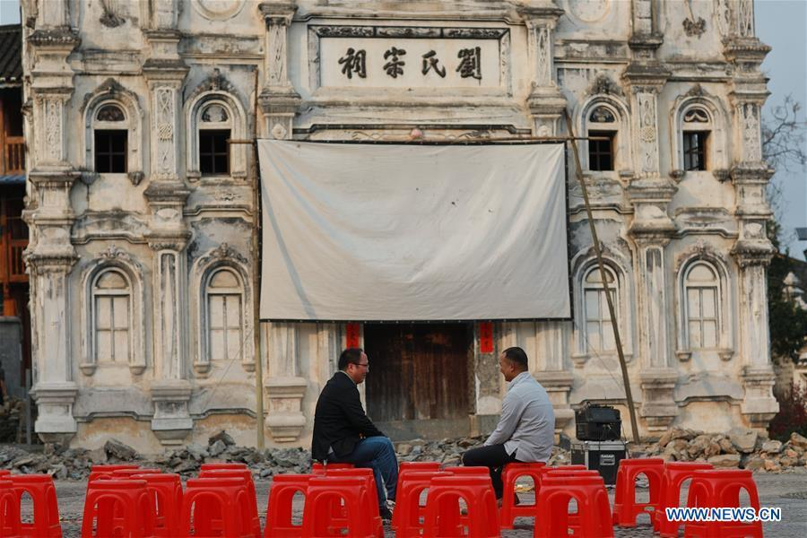 Huang Yiyin (L) and his assistant Wang Yangqing chat before screening a movie in Santangmen Village of Benchu Town, Tianzhu County of Miao and Dong Autonomous Prefecture of Qiandongnan, southwest China\'s Guizhou Province, March 19, 2019. Local authority in Tianzhu County established special fund to show movies in rural areas. In 2018, a total of 14 voluntary projectionists in Tianzhu showed 3,979 movies in villages within the county. (Xinhua/Ou Dongqu)