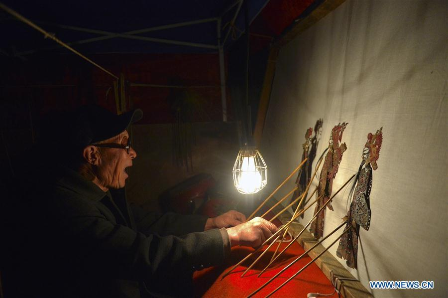 Chang Bingzhang plays the shadow puppet performance at Luyuan Township of Weiyuan County in Dingxi City, northwest China\'s Gansu province, March 12, 2019. Many local folk artists concentrate on inheriting and passing down the folk art of shadow puppet performing and making in Gansu. They devote themselves to the study of the art and also organize various events to popularize the art. (Xinhua/Li Xiao)