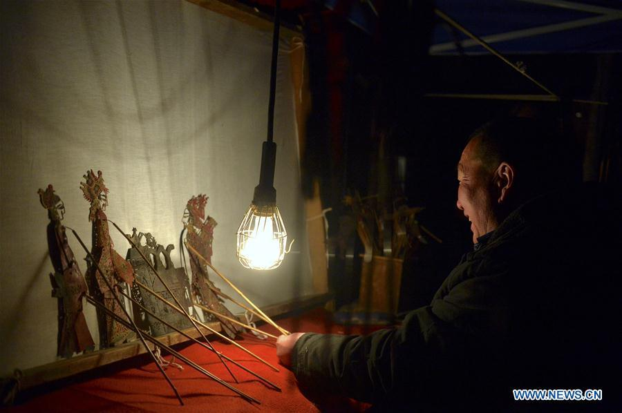 Zhang Guobin plays the shadow puppet performance at Luyuan Township of Weiyuan County in Dingxi City, northwest China\'s Gansu province, March 12, 2019. Many local folk artists concentrate on inheriting and passing down the folk art of shadow puppet performing and making in Gansu. They devote themselves to the study of the art and also organize various events to popularize the art. (Xinhua/Li Xiao)
