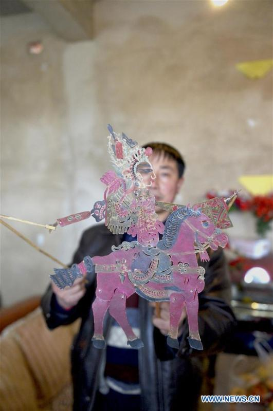 Pan Mingsheng displays shadow puppet made by himself at Xinzhai Township of Weiyuan County in Dingxi City, northwest China\'s Gansu province, March 13, 2019. Many local folk artists concentrate on inheriting and passing down the folk art of shadow puppet performing and making in Gansu. They devote themselves to the study of the art and also organize various events to popularize the art. (Xinhua/Li Xiao)
