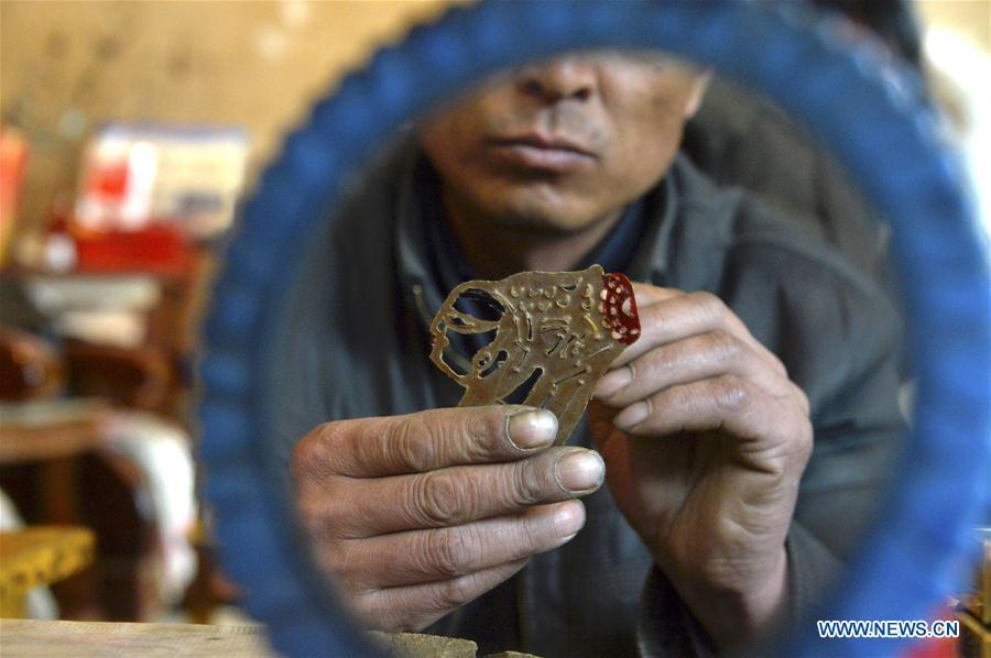 Zhou Zhibing, the apprentice of Pan Mingsheng, applies dye to the shadow puppet at Xinzhai Township of Weiyuan County in Dingxi City, northwest China\'s Gansu province, March 13, 2019. Many local folk artists concentrate on inheriting and passing down the folk art of shadow puppet performing and making in Gansu. They devote themselves to the study of the art and also organize various events to popularize the art. (Xinhua/Li Xiao)