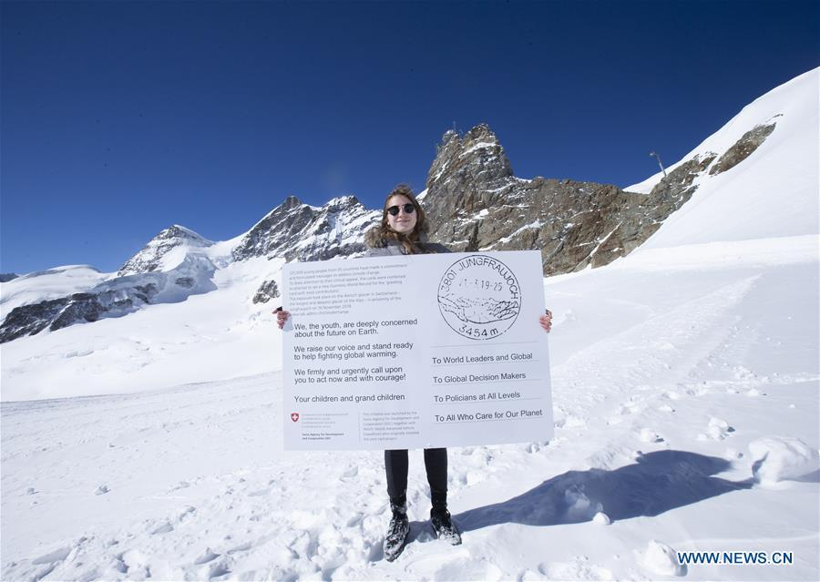 Swiss teenager Selma Schellenberg shows a copy of a postcard calling for action against climate change on the Aletsch glacier under Jungfraujoch in Switzerland, on March 20, 2019. Some 900 postcards from youths all over the world were stamped and sent on Wednesday from Europe\'s highest postbox on the Jungfraujoch peak, Switzerland, to global leaders, calling for action against climate change. (Xinhua/Xu Jinquan)
