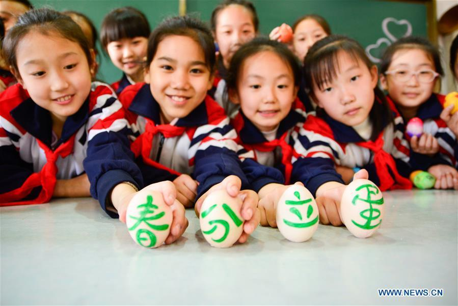 Students play a game to make eggs stand upright on end at a primary school in Handan, north China\'s Hebei Province, March 20, 2018, one day ahead of \