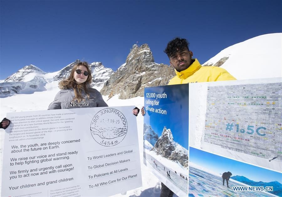 Swiss teenagers Sarangan Sivarajalingam (R) and Selma Schellenberg show copies of a postcard calling for action against climate change on the Aletsch glacier under Jungfraujoch in Switzerland, on March 20, 2019. Some 900 postcards from youths all over the world were stamped and sent on Wednesday from Europe\'s highest postbox on the Jungfraujoch peak, Switzerland, to global leaders, calling for action against climate change. (Xinhua/Xu Jinq