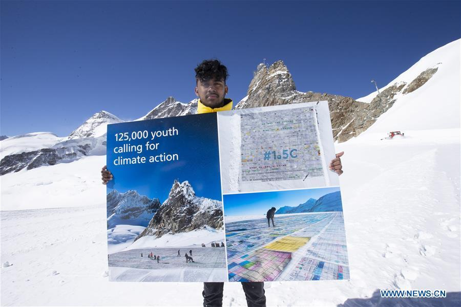 Swiss teenager Sarangan Sivarajalingam shows a copy of a postcard calling for action against climate change on the Aletsch glacier under Jungfraujoch in Switzerland, on March 20, 2019. Some 900 postcards from youths all over the world were stamped and sent on Wednesday from Europe\'s highest postbox on the Jungfraujoch peak, Switzerland, to global leaders, calling for action against climate change. (Xinhua/Xu Jinquan)
