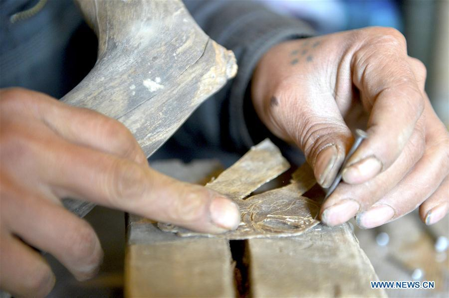 Zhou Zhibing, the apprentice of Pan Mingsheng, carves the shadow puppet at Xinzhai Township of Weiyuan County in Dingxi City, northwest China\'s Gansu province, March 13, 2019. Many local folk artists concentrate on inheriting and passing down the folk art of shadow puppet performing and making in Gansu. They devote themselves to the study of the art and also organize various events to popularize the art. (Xinhua/Li Xiao)