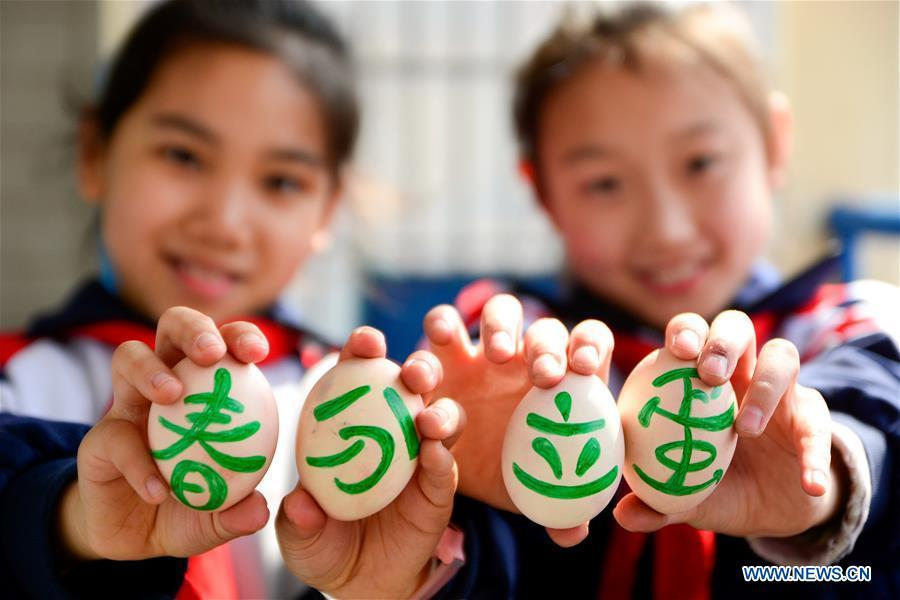 Students display their painted eggs as a part of the game at a primary school in Handan, north China\'s Hebei Province, March 20, 2018, one day ahead of \