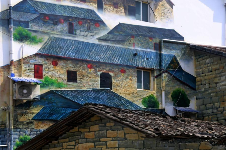 Spring brings beautiful scenery to Puxihe village in Yichang city, Hubei province, March 15, 2019. As the weather becomes warmer, golden cole flowers are blossoming in the region. Meanwhile, local residences are painted with images of animals and agricultural activities, adding liveliness to the landscape. (Photo/Asianewsphoto)
