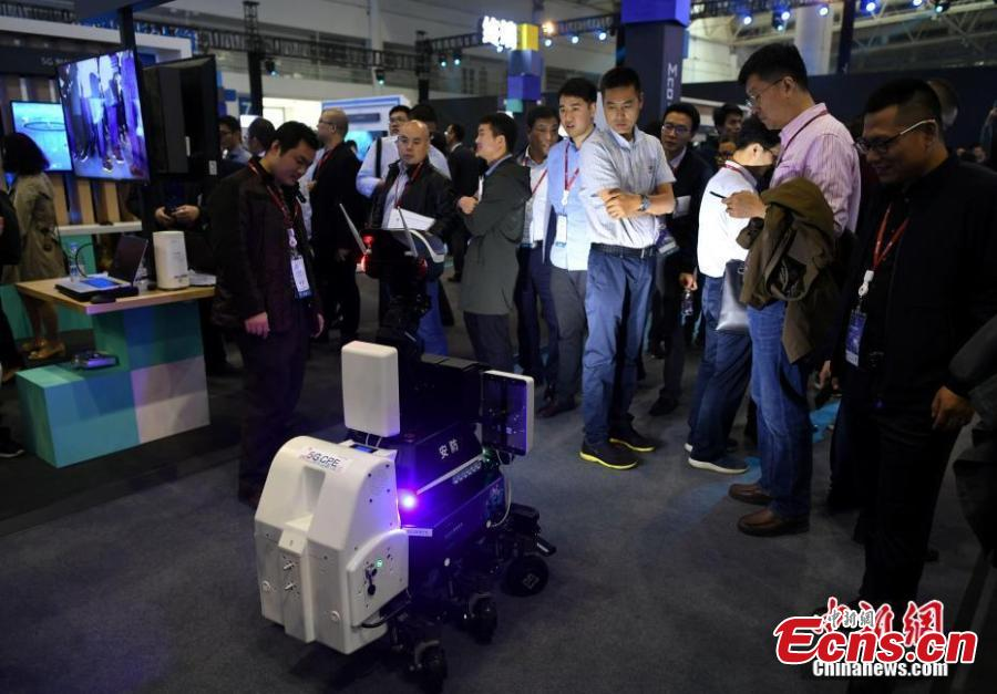 People look at a security robot during the Huawei China Eco-Partner Conference 2019 at the Fuzhou Strait International Conference & Exhibition Center in Fuzhou, Fujian Province, March 21, 2019. (Photo: China News Service/Wang Dongming)