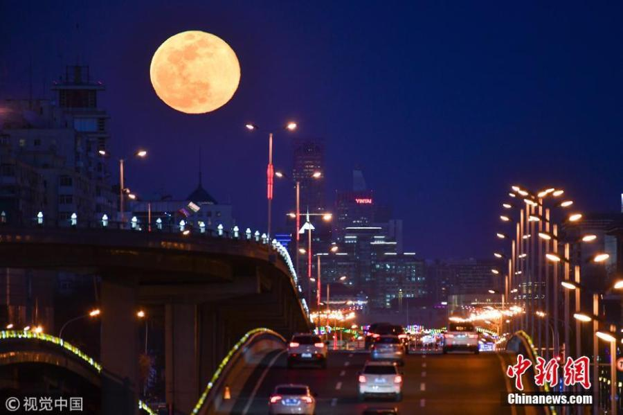 A super snow moon rises over Chang\'an Avenue, a major thoroughfare in Beijing, March 21, 2019. Sky-watchers received a treat as the final supermoon of 2019 arrived on Thursday, also the Spring Equinox, which signals the equal length of day and night time. A supermoon occurs when a full moon\'s orbit is closest to the Earth.  (Photo/VCG)