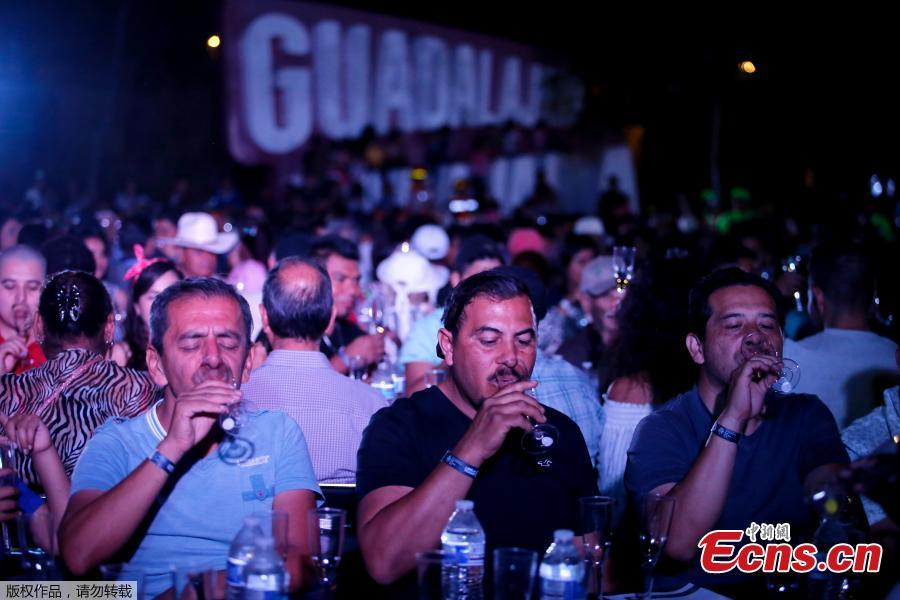 People drink tequila as 1,486 people gather to hold a tequila tasting at the Plaza Liberacion in Guadalajara, Jalisco, Mexico, on March 24, 2019 in an attempt to set a new Guinness World Record for the \
