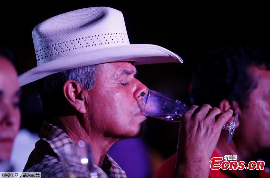 A man drinks tequila as 1,486 people gather to hold a tequila tasting at the Plaza Liberacion in Guadalajara, Jalisco, Mexico, on March 24, 2019 in an attempt to set a new Guinness World Record for the \