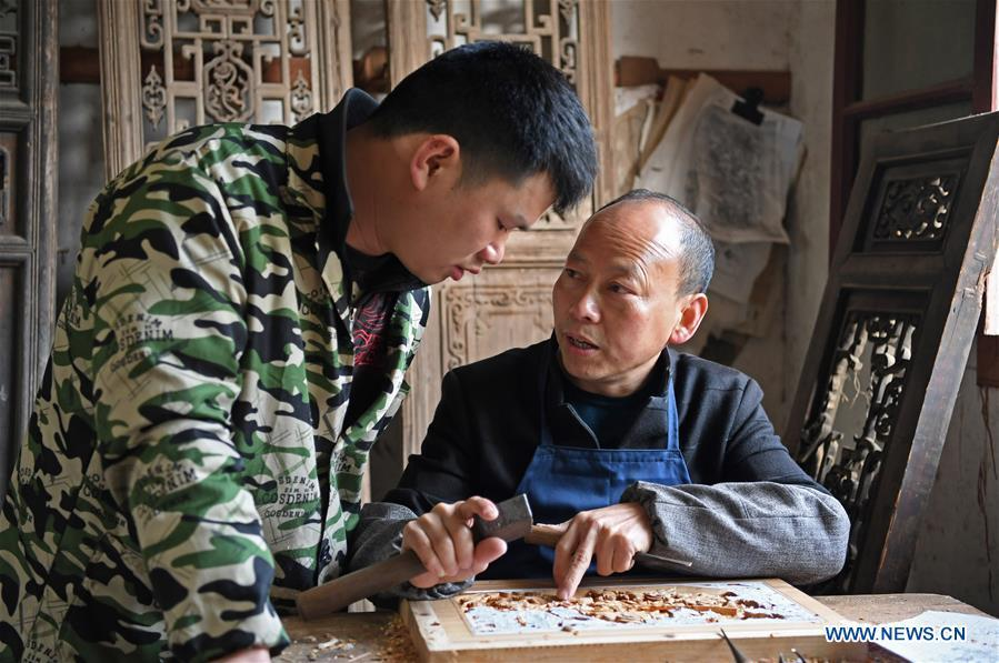 Yu Youhong teaches his apprentice the techniques on carvings in Wuyuan County of east China\'s Jiangxi Province, March 19, 2019. The \