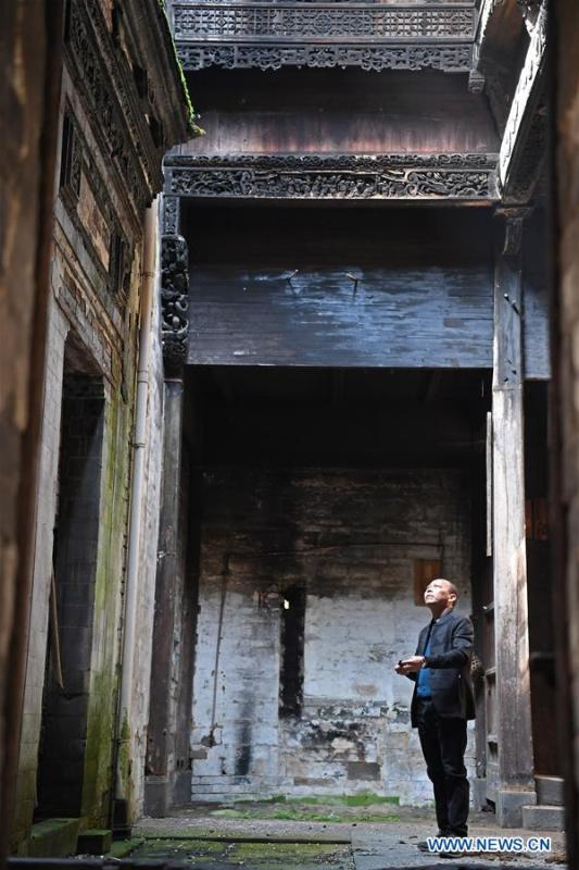 Yu Youhong checks a dilapidated ancient building in Wangkou Village, Wuyuan County of east China\'s Jiangxi Province, March 19, 2019. The \