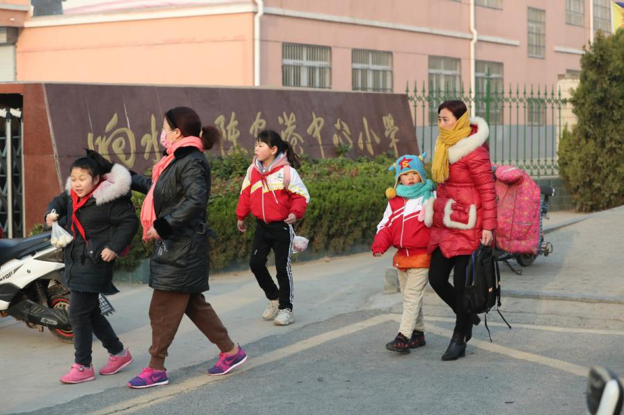Parents send their children to school in Xiangshui county in Yancheng, Jiangsu province, on March 25, 2019. An industrial park explosion occurred in the county on March 21, killing 78. (Photo/chinadaily.com.cn)