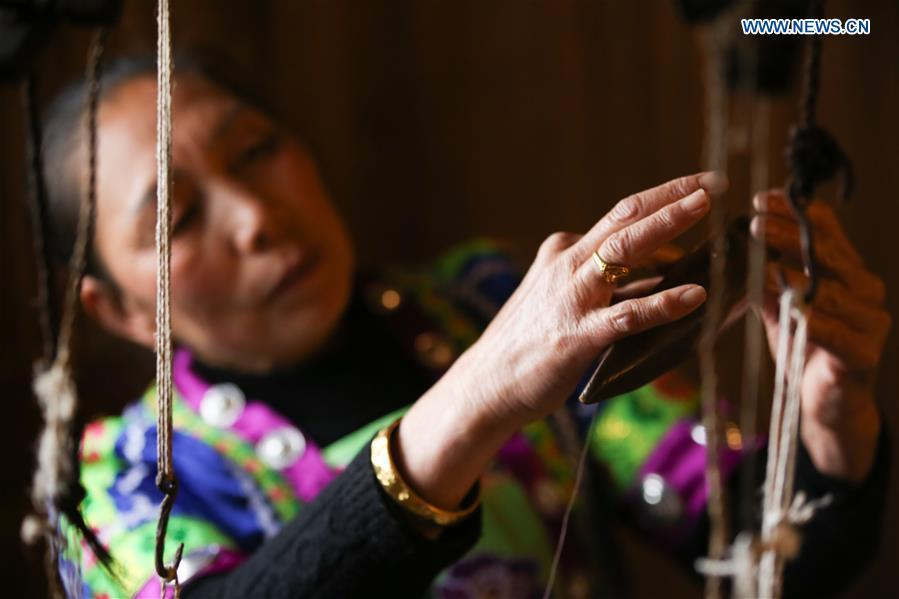 A woman of Dong ethnic group arranges the shuttle of the loom at Laozhai Village of Yuping Dong Autonomous county of Tongren, southwest China\'s Guizhou Province, March 23, 2019. Traditional Dong cloth making has a long history. The procedure includes planting cotton, spinning, weaving, dyeing, etc. And the cloth enjoys lasting popularity among the people of Dong ethnic group. (Xinhua/Luo Dafu)