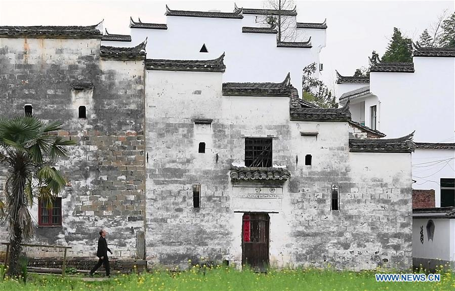 Yu Youhong walks past an ancient building in Zhangcun Village, Wuyuan County of east China\'s Jiangxi Province, March 19, 2019. The \