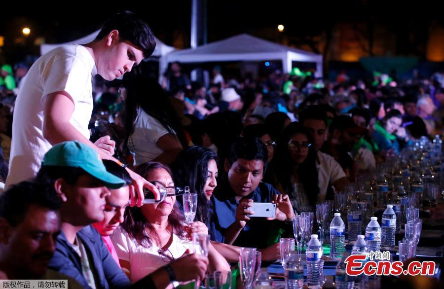 A man serves tequila as 1,486 people gather to hold a tequila tasting at the Plaza Liberacion in Guadalajara, Jalisco, Mexico, on March 24, 2019 in an attempt to set a new Guinness World Record for the \