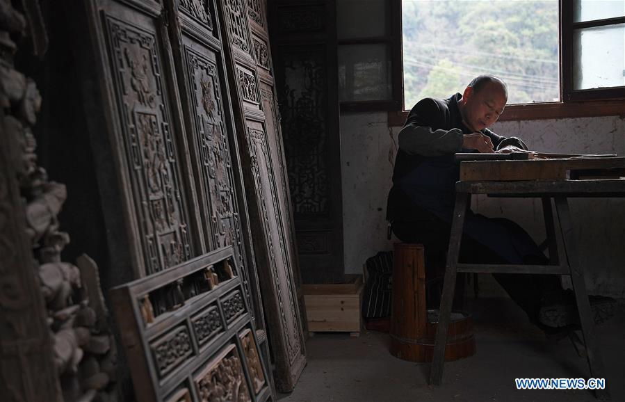 Yu Youhong makes carvings on wood at his studio in Wangkou Village, Wuyuan County of east China\'s Jiangxi Province, March 18, 2019. The \