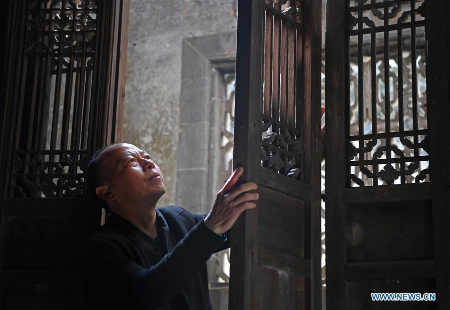 Yu Youhong checks a part of an ancient building in Wangkou Village, Wuyuan County of east China\'s Jiangxi Province, March 19, 2019. The \