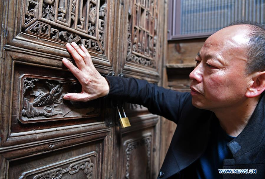 Yu Youhong checks a broken carving work on wood inside an ancient building in Zhangcun Village, Wuyuan County of east China\'s Jiangxi Province, March 19, 2019. The \