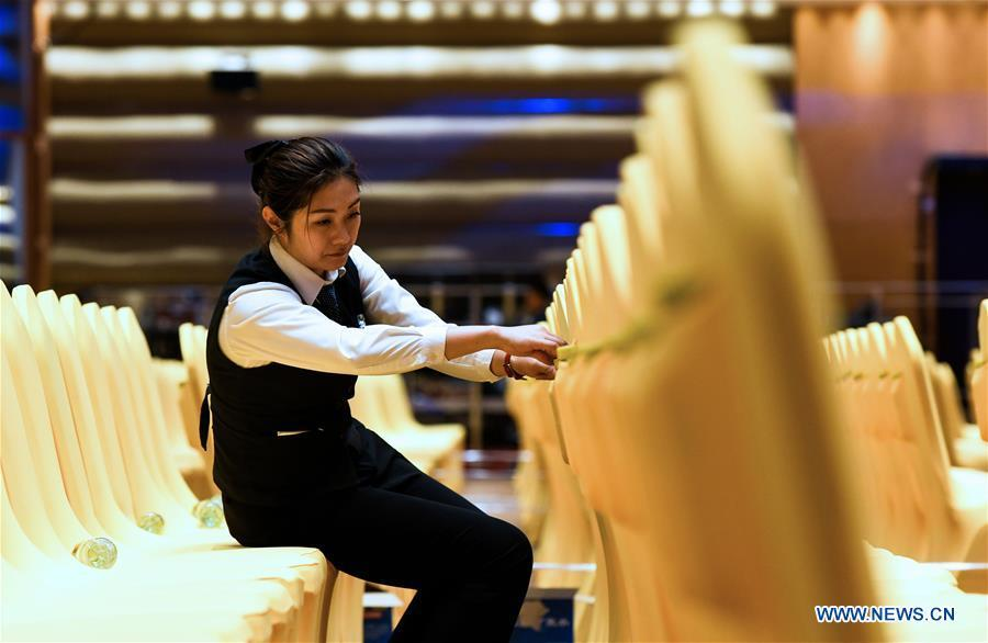 A staff member checks chairs in the main venue of the Boao Forum for Asia (BFA) in Boao Town of Qionghai City, south China\'s Hainan Province, March 24, 2019. The BFA annual conference will be held in Boao from March 26 to 29 under the theme of \