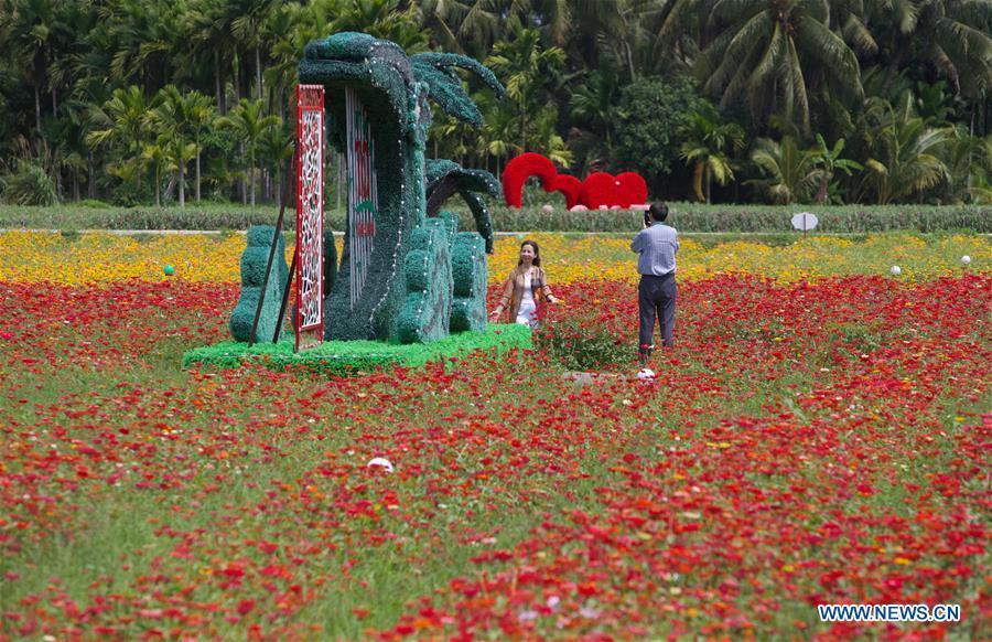 A visitor poses for photos at a garden in Nanqiang Village, Boao Town, Qionghai City of south China\'s Hainan Province, March 25, 2019. Qionghai City has quickened its steps towards the construction of \