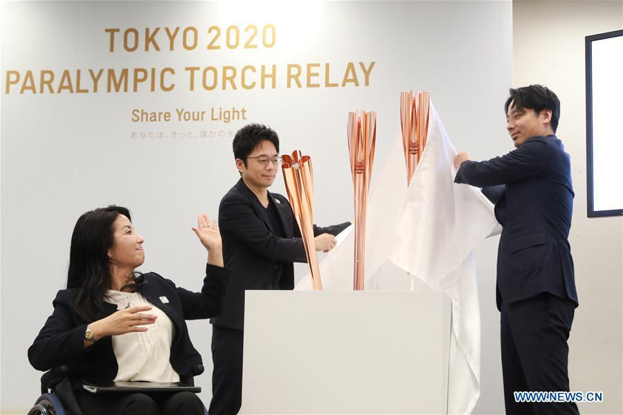 Tokyo 2020 Torch Relay Offical Ambassador Aki Taguchi (L), torch designer Tokujin Yoshioka (C) and Tokyo 2020 Athletes\' Commission member Shintaro Ikeda unveil the samples of the Tokyo 2020 Olympic Torch in Tokyo, Japan, on March 25, 2019. Tokyo 2020 unveiled the sample of the Tokyo 2020 Paralympic Torch on Monday. The color of Tokyo 2020 Paralympic Torch is cherry blossom pink. Aluminum recycled from temporary housing used in areas struck by the Great East Japan Earthquake disaster will be used to manufacture the torch. (Xinhua/Du Xiaoyi)