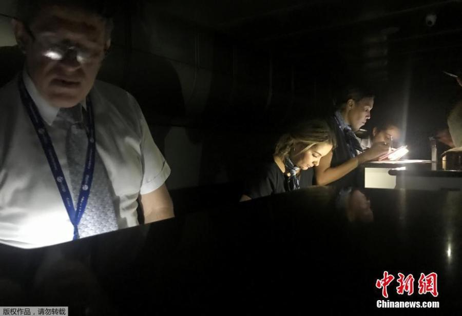 Employees check the boarding passes during a blackout at Simon Bolivar international airport in Caracas, Venezuela March 25, 2019. (Photo/Agencies)