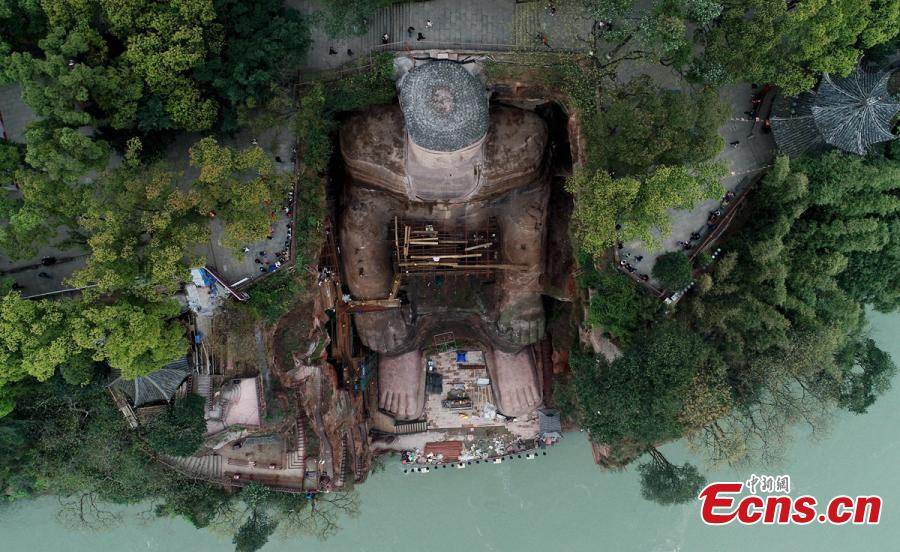 Work continues to restore the Giant Buddha of Leshan in Sichuan Province, March 25, 2019. Standing 71 meters high, the statue was carved out of a hillside in the 8th century and looks down on the confluence of three rivers. It will reopen to tourists on April 1 after undergoing repairs for the past six months. Mount Emei Scenic Area, including the Leshan Giant Buddha, was inscribed as a UNESCO world heritage site in 1996. (Photo: China News Service/Liu Zhongjun)
