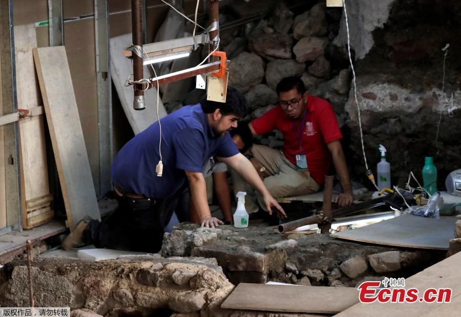 Miguel Baez (L) and Antonio Marin, archaeologists with the National Institute of Anthropology and History (INAH), work at a site where the 500-year-old interior of a partially-excavated stone box shows an Aztec offering that includes the bones of a jaguar with the circular emblem of the war god Huitzilopochtli, as well a layer of coral, the remains of a large number of starfish and shells and found at the steps of the Templo Mayor in downtown Mexico City, Mexico, March 14, 2019. (Photo/Agencies)