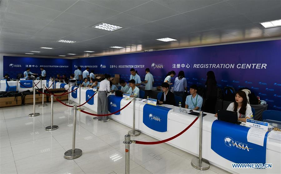 Staff members work at the registration center of the Boao Forum for Asia (BFA) in Boao Town of Qionghai City, south China\'s Hainan Province, March 25, 2019. The BFA annual conference will be held in Boao from March 26 to 29 under the theme of \