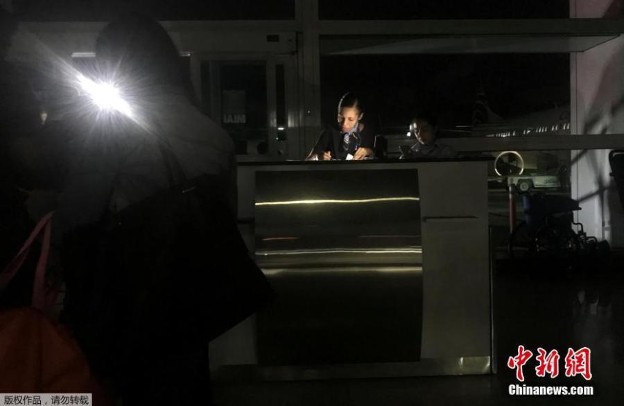 An employee checks boarding passes during a blackout at Simon Bolivar international airport in Caracas, Venezuela March 25, 2019.  (Photo/Agencies)