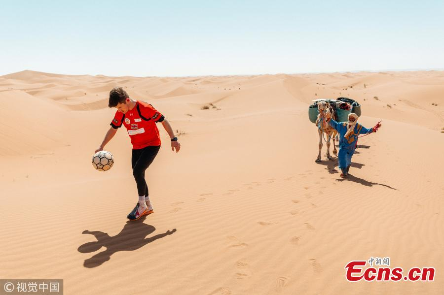 Freestyle footballer John Farnworth battled a sandstorm and 40C heat to play \'keepie-uppies\' across 60 miles of the Sahara. He juggled a ball in the air more than 250,000 times over the course of six days across the African desert in a bid to break his ninth world record. Farnworth worn goggles and specially designed trainers to keep sand out during the storm. Joined by three friends, he enlisted the help of four Moroccans to help navigate across the sprawling landscape. (Photo/VCG)