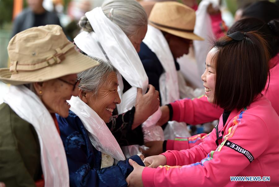 Young people present hada, a white ceremonial silk scarf, to the elderly in an event to celebrate the 60th anniversary of democratic reforms in Tibet, at a community in Lhasa, capital of southwest China\'s Tibet Autonomous Region, March 23, 2019. (Xinhua/Chogo)