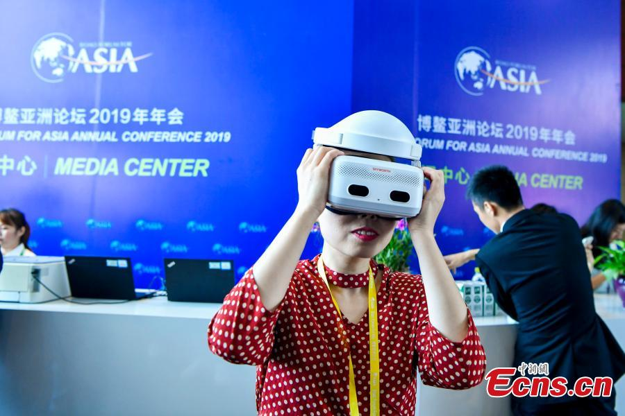 A reporter wears virtual reality (VR) goggles at the media center of the Boao Forum for Asia annual conference in Boao, Hainan Province, March 26, 2019. China Telecom showcased its 5G service at the media center, allowing 4K ultra-high-definition reports from the event, being held from March 26 to 29. Boao is one of two places in the island province where China Telecom is testing the 5G service. (Photo: China News Service/Luo Yunfei)