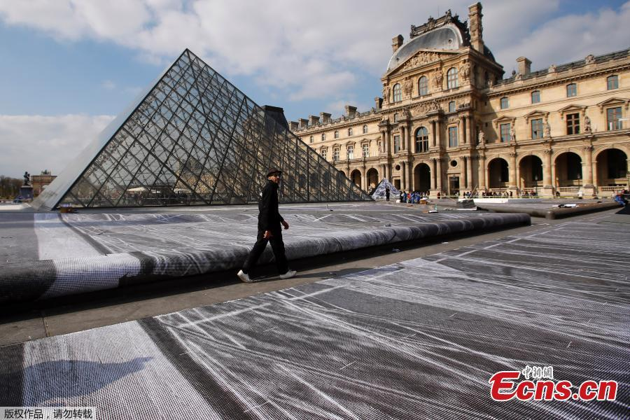 French artist JR works in the courtyard of the Louvre Museum near the glass pyramid designed by Ieoh Ming Pei as the Louvre Museum celebrates the 30th anniversary of its glass pyramid in Paris, France, March 26, 2019.  (Photo/Agencies)