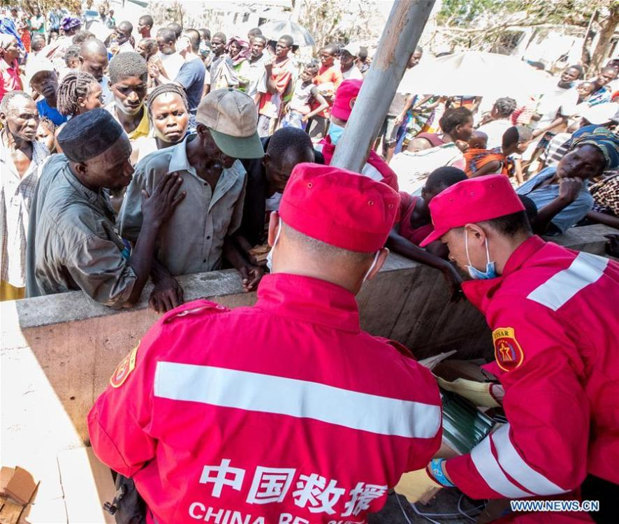 Members of Chinese rescue team distribute disaster relief goods in Lamago Village, 90 km from Beira, Mozambique, March 26, 2019. A Chinese rescue team went to Lamago Village to carry out disaster relief work on Tuesday. (Xinhua/Zhang Yu)