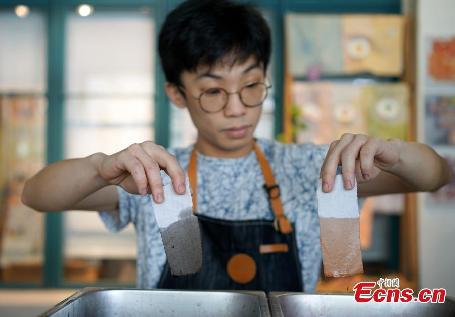 Eric Cheung, founder of Dyelicious, compares the colors made from materials such as leftover food and plants in Hong Kong. (Photo: China News Service/Zhang Wei)