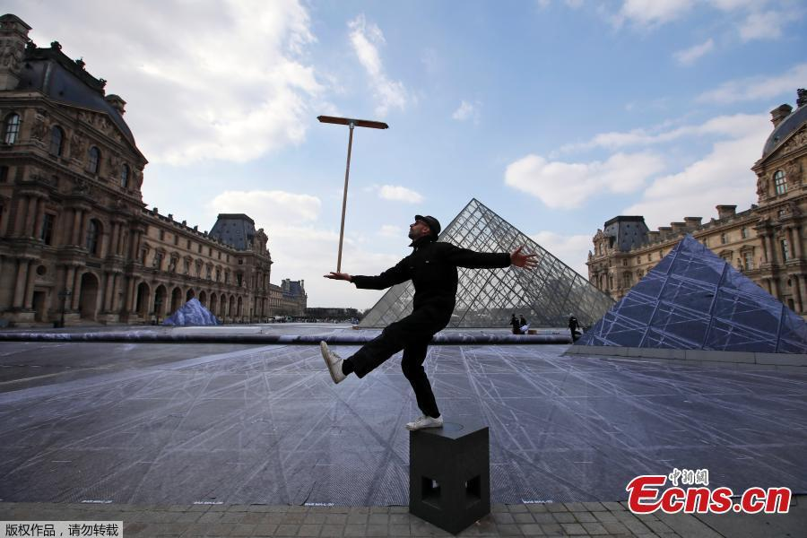 French artist JR performs in the courtyard of the Louvre Museum near the glass pyramid designed by Ieoh Ming Pei as the Louvre Museum celebrates the 30th anniversary of its glass pyramid in Paris, France, March 26, 2019.  (Photo/Agencies)