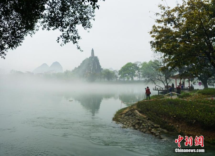 A view of Tashan Mountain surrounded by mist along the riverbanks of the Lijiang River in Guilin City, Guangxi Zhuang Autonomous Region, March 28, 2019. Like a green ribbon flowing through the mountains, the Lijiang River is known for its amazing natural beauty. (Photo: China News Service/Tang Mengxian)