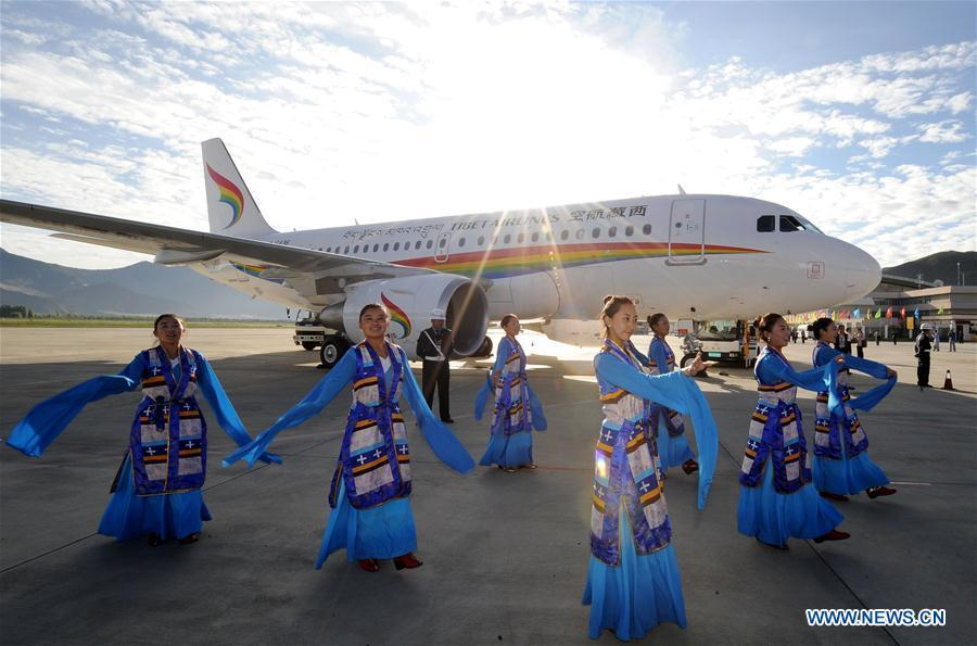 Performers give a dance performance beside a plane of the Tibet Airlines which prepares to take off at the Lhasa Gonggar Airport, southwest China\'s Tibet Autonomous Region, July 26, 2011. Infrastructure has been improved in Tibet, as a comprehensive transportation network composed of highways, railways and air routes has been formed. (Xinhua/Chogo)