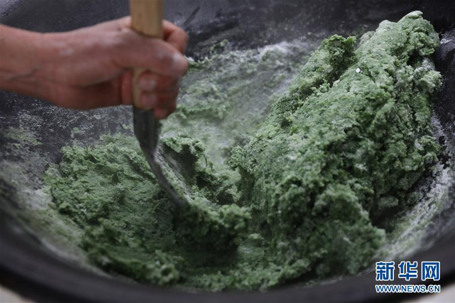 Wild mugwort is pounded before being added to glutinous rice and molded into smooth, silky qingtuan cakes. (Photo/Xinhua)
