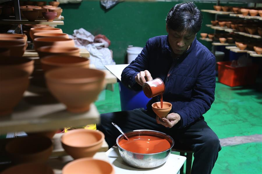 Wu Lizhu, inheritor of the workmanship of Jianzhan teaware, glazes a piece of porcelain at his workshop in Jianyang District of Nanping City, south China\'s Fujian Province, March 28, 2019. Jianzhan teaware, a well-known Chinese porcelain originated in Jianyang, dates back to more than 1,000 years ago in Song dynasty (960-1279). It was the best teaware for scholars and literati to use during that time in tea competitions. Jianzhan teawares are known for their variability. Glazes can range in color from dark plum to yellow, green, and blue. During the heating and cooling processes, iron element in the clay can migrate within the glaze to form surface crystals in rich and glossy colors, as in the \