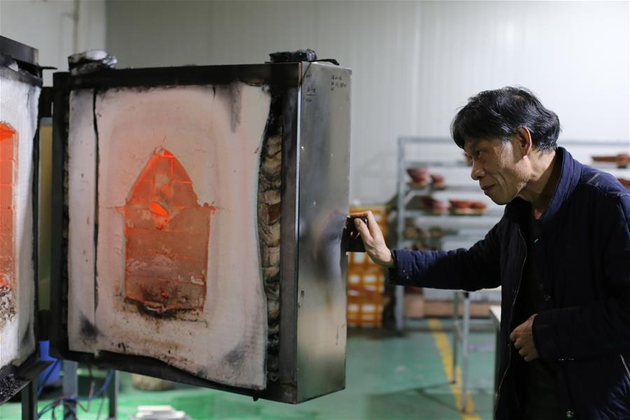 Wu Lizhu, inheritor of the workmanship of Jianzhan teaware, observes pieces of porcelain in the kiln at his workshop in Jianyang District of Nanping City, south China\'s Fujian Province, March 28, 2019. Jianzhan teaware, a well-known Chinese porcelain originated in Jianyang, dates back to more than 1,000 years ago in Song dynasty (960-1279). It was the best teaware for scholars and literati to use during that time in tea competitions. Jianzhan teawares are known for their variability. Glazes can range in color from dark plum to yellow, green, and blue. During the heating and cooling processes, iron element in the clay can migrate within the glaze to form surface crystals in rich and glossy colors, as in the \