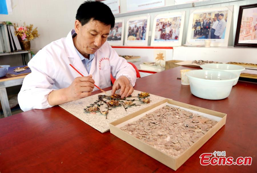 Wang Zhongxiang uses discarded jade fragments to make handicrafts in Qilian County, Northwest China\'s Qinghai Province, March 28, 2019. The 55-year-old folk artist is known for his ability to turn the waste into valuable works of art often through time-consuming processes, such as polishing, painting and pasting. (Photo: China News Service/Ma Mingyan)