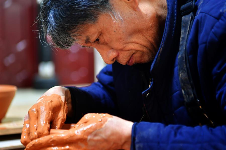 Wu Lizhu, inheritor of the workmanship of Jianzhan teaware, makes a piece of porcelain at his workshop in Jianyang District of Nanping City, south China\'s Fujian Province, March 28, 2019. Jianzhan teaware, a well-known Chinese porcelain originated in Jianyang, dates back to more than 1,000 years ago in Song dynasty (960-1279). It was the best teaware for scholars and literati to use during that time in tea competitions. Jianzhan teawares are known for their variability. Glazes can range in color from dark plum to yellow, green, and blue. During the heating and cooling processes, iron element in the clay can migrate within the glaze to form surface crystals in rich and glossy colors, as in the \