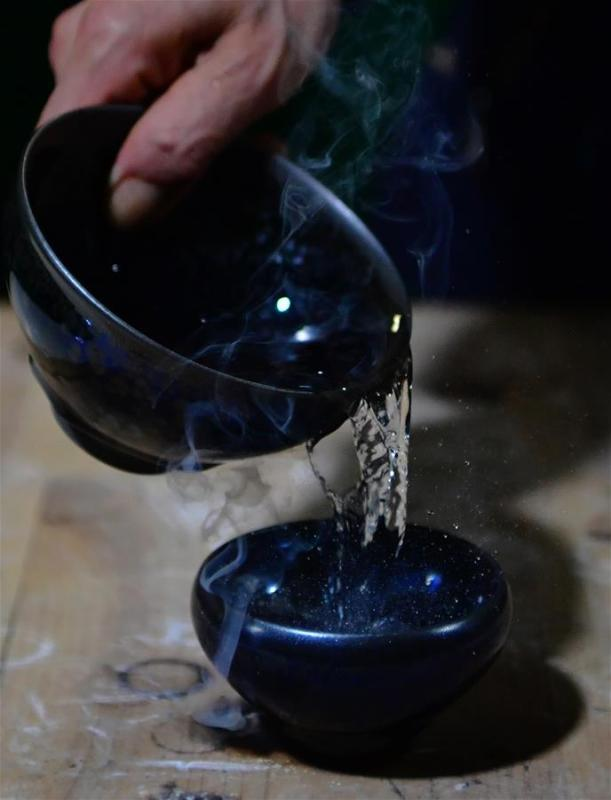 Wu Lizhu, inheritor of the workmanship of Jianzhan teaware, cools a piece of porcelain at his workshop in Jianyang District of Nanping City, south China\'s Fujian Province, March 28, 2019. Jianzhan teaware, a well-known Chinese porcelain originated in Jianyang, dates back to more than 1,000 years ago in Song dynasty (960-1279). It was the best teaware for scholars and literati to use during that time in tea competitions. Jianzhan teawares are known for their variability. Glazes can range in color from dark plum to yellow, green, and blue. During the heating and cooling processes, iron element in the clay can migrate within the glaze to form surface crystals in rich and glossy colors, as in the \